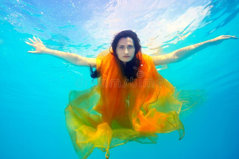A beautiful girl underwater with a yellow cloth looks and poses for the camera on a Sunny day, arms outstretched royalty free stock image