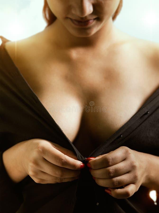 Beautiful girl undressing herself stock photography