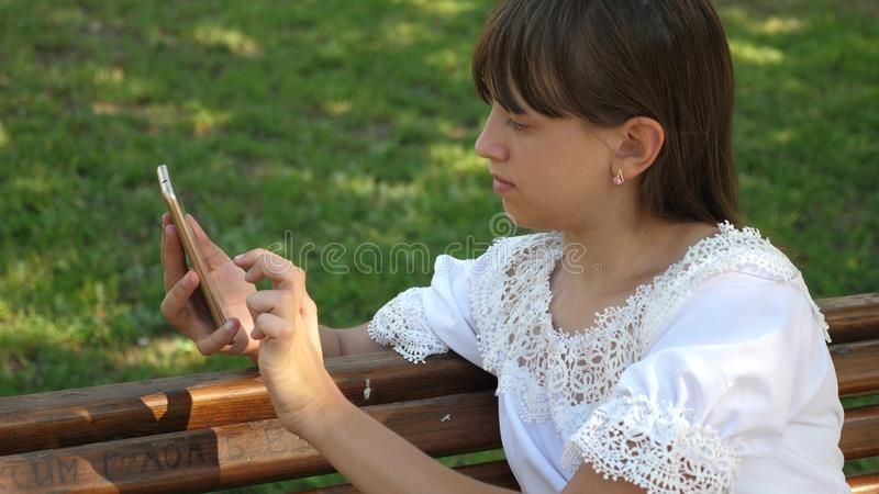Beautiful girl using a smartphone is writing a letter on a bench in a beautiful green park. Slow motion. Young. Beautiful girl using a smartphone is writing a royalty free stock image