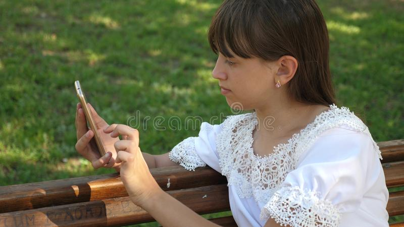 Beautiful girl using a smartphone is writing a letter on a bench in a beautiful green park. Slow motion. Young. Beautiful girl using a smartphone is writing a royalty free stock photo