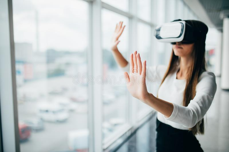 Beautiful girl using virtual reality glasses near bright window with skyscraper view outside. Business woman wearing VR goggles stock photography