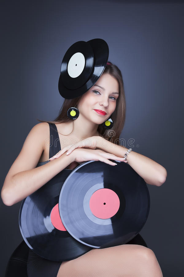 Beautiful girl with vinyl disc on black background. Beautiful girl wearing hat with two vinyl disc on black background stock photography