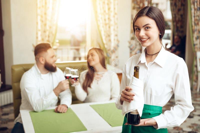 Beautiful girl waiter holds open bottle of wine stock images