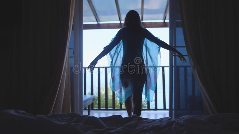 Beautiful girl waking up opens curtains and go to sea view terrace. Young woman looking at amazing landscape horizon royalty free stock photos