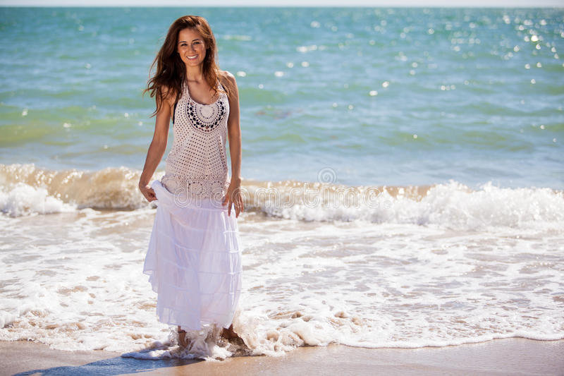 Beautiful girl walking on the beach. Pretty Latin brunette walking near the water at the beach royalty free stock image