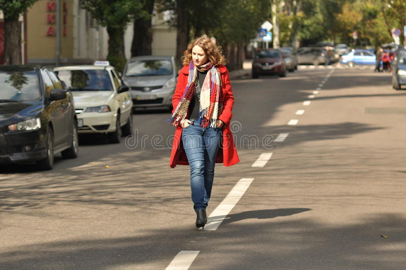 Beautiful girl walking on city road royalty free stock image
