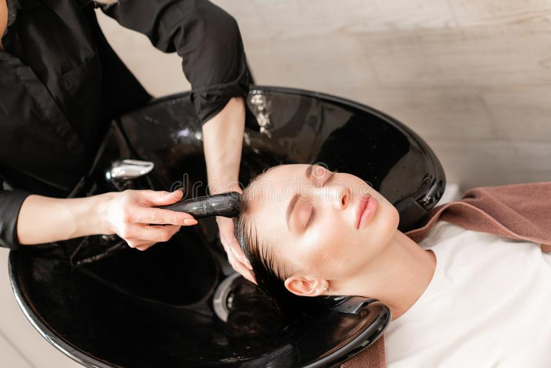 Beautiful girl washes her hair before a haircut in a beauty salon. hair washing at a hairdressing. professional shampoo royalty free stock photography