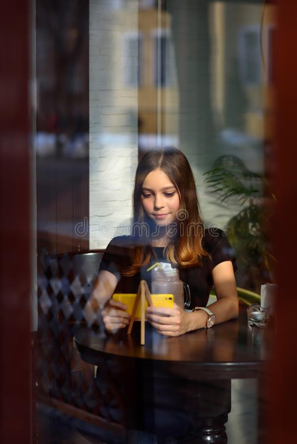 Girl drinks coffee and watches video on mobile phone stock photography