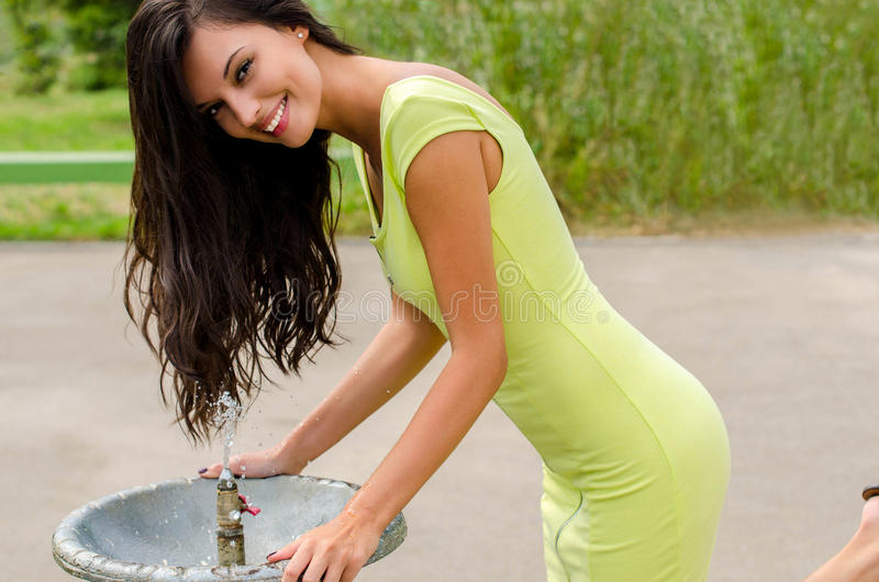Beautiful girl at water fountain royalty free stock image