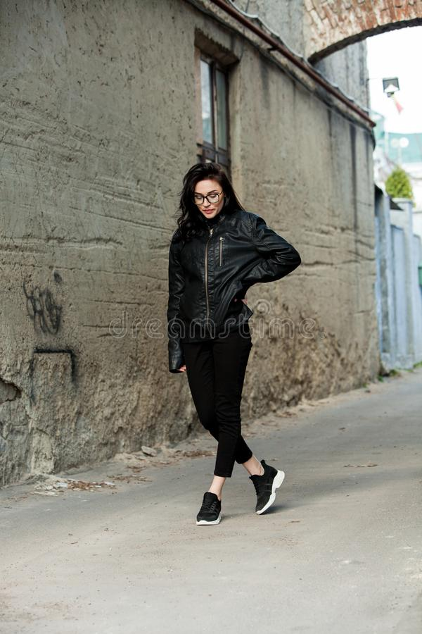 Beautiful girl with wavy hair in black leather jacket. Portrait of cute young business woman outdoor royalty free stock photography