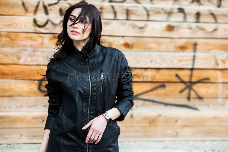 Beautiful girl with wavy hair in black leather jacket. Portrait of cute young business woman outdoor stock photo