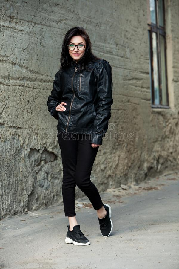 Beautiful girl with wavy hair in black leather jacket. Portrait of cute young business woman outdoor royalty free stock photo
