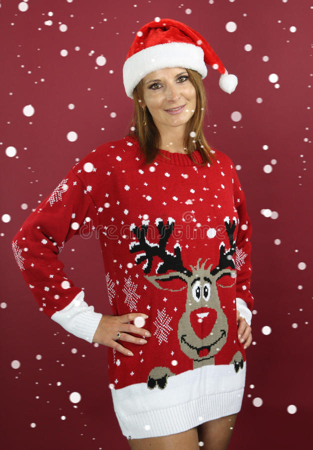 Beautiful girl wearing a christmas pull. Beautiful girl wearing a santa hat over a gray background royalty free stock image