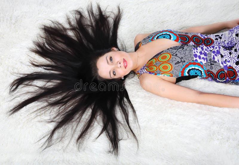 Beautiful girl wearing dress lies on white fur royalty free stock images