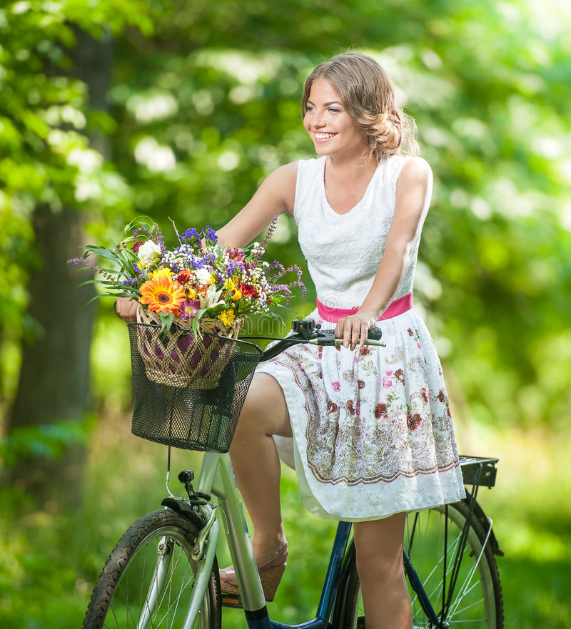 Beautiful girl wearing a nice white dress having fun in park with bicycle. Healthy outdoor lifestyle concept. Vintage scenery. Pretty blonde girl with retro royalty free stock image