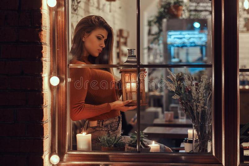A beautiful girl wearing sweater holding a candle lantern while sitting on a window sill inside the cafe stock photo