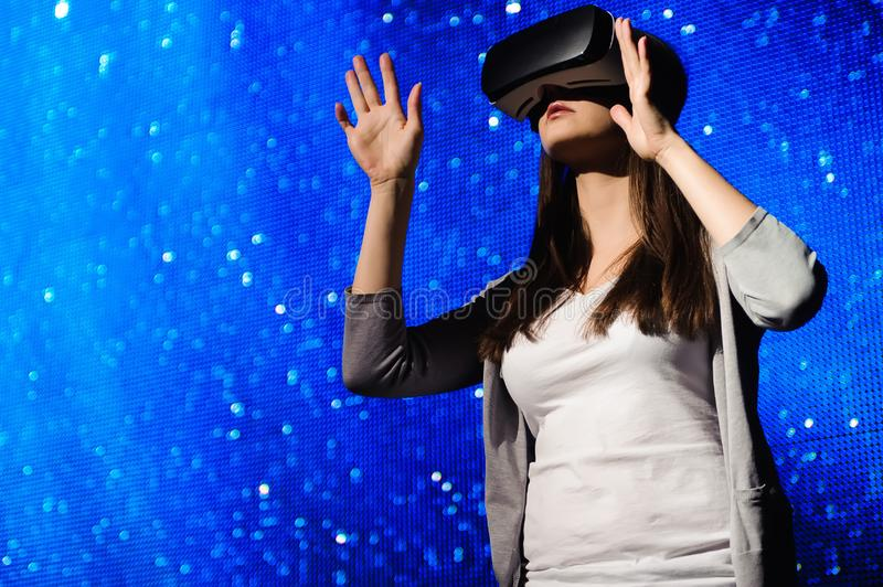 A beautiful girl wearing a virtual reality device, standing on the background of the sky. A beautiful girl wearing a virtual reality device, standing on the royalty free stock photography
