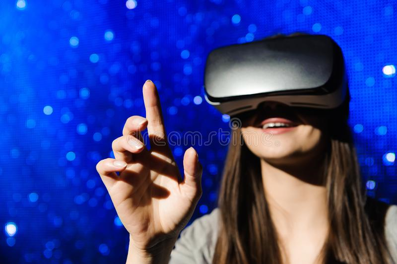 A beautiful girl wearing a virtual reality device, standing on the background of the sky. A beautiful girl wearing a virtual reality device, standing on the royalty free stock image