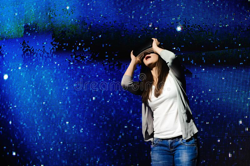A beautiful girl wearing a virtual reality device, standing on the background of the sky. A beautiful girl wearing a virtual reality device, standing on the royalty free stock images