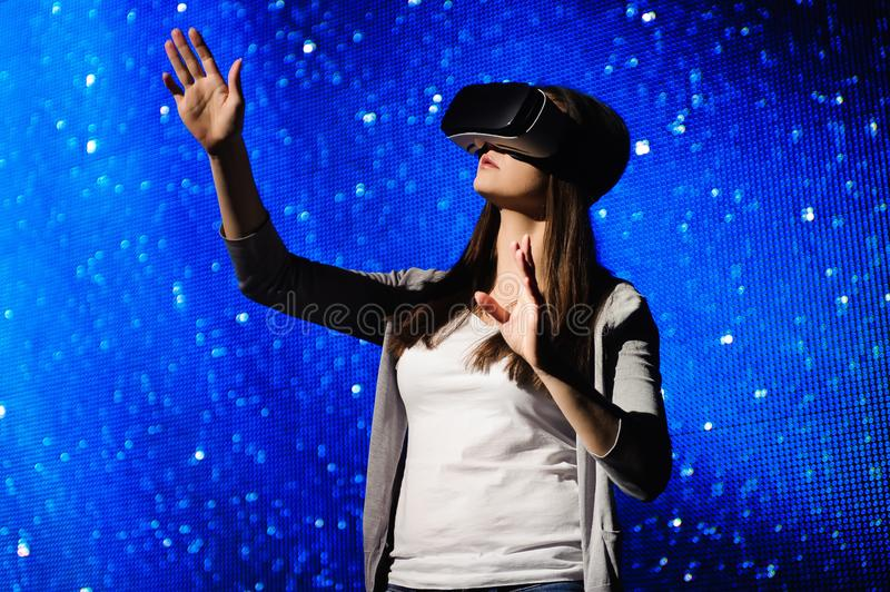 A beautiful girl wearing a virtual reality device, standing on the background of the sky. A beautiful girl wearing a virtual reality device, standing on the stock photography