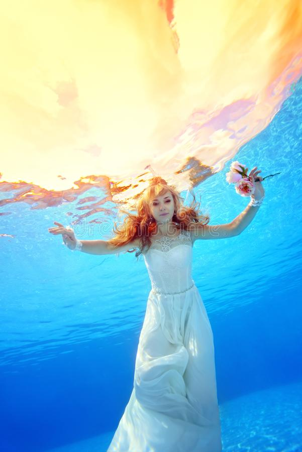 Beautiful girl in wedding dress swims underwater in the pool at sunset with flowers in his hands stock images