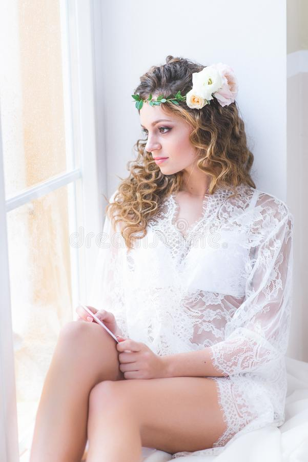 Beautiful girl in a white bridal negligee sitting stock photo