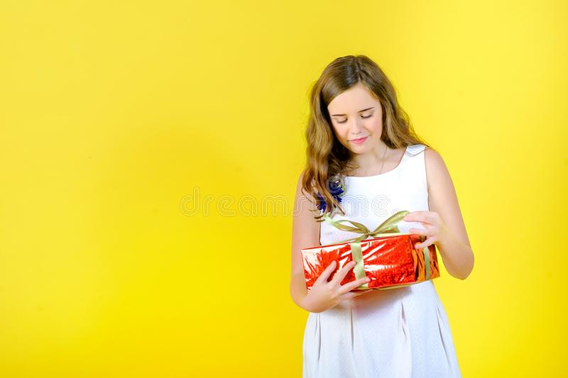 Beautiful girl in a white dress unties the ribbon and opens the gift. The gift box is wrapped with bright red paper, in the studio on a yellow background royalty free stock image