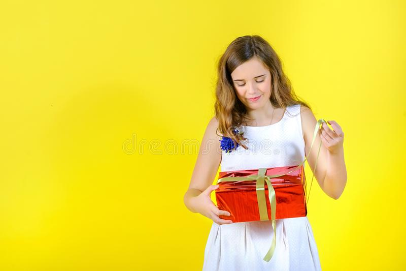 Beautiful girl in a white dress unties the ribbon and opens the gift. The gift box is wrapped with bright red paper, in the studio on a yellow background royalty free stock photography