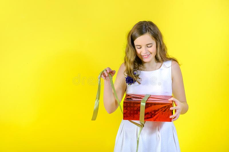 Beautiful girl in a white dress unties the ribbon and opens the gift. Beautiful girl in white dress unties the ribbon and opens the gift, on yellow background stock photo