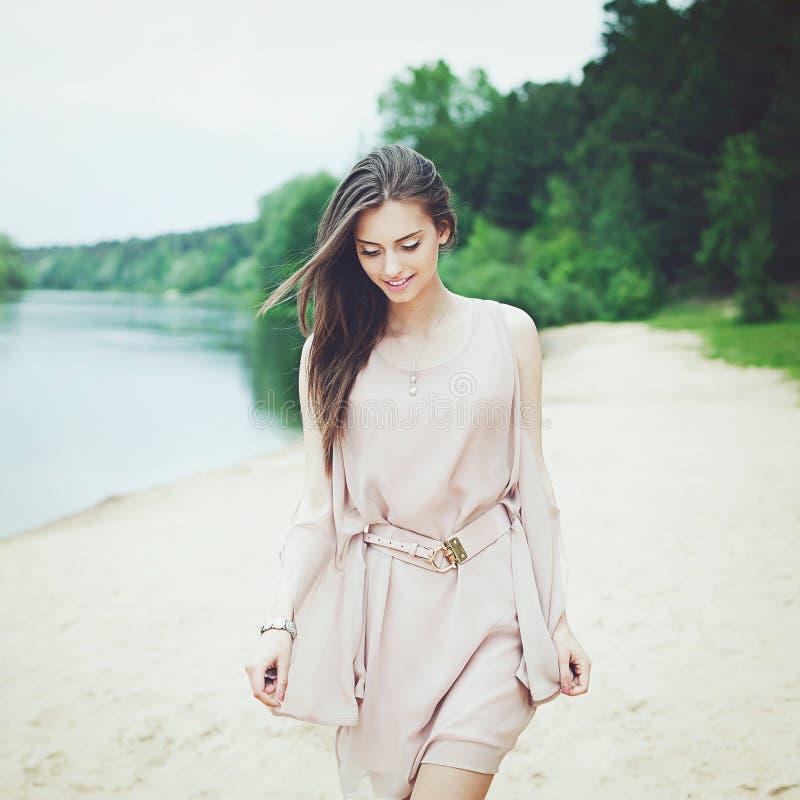 Beautiful girl in white dress walking near a lake stock photo