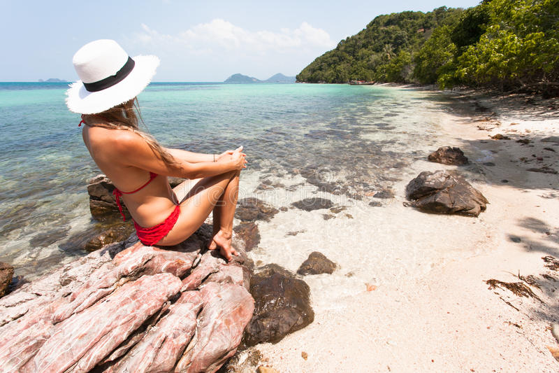Beautiful Girl White Hair and red swimmingsuit sitting on rock beach, relaxing and enjoy freedom. royalty free stock photo