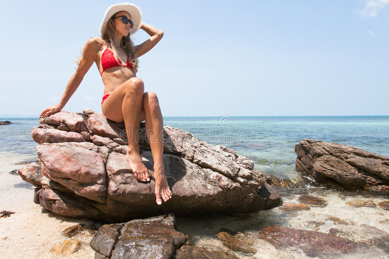 Beautiful Girl White Hair and red swimmingsuit sitting on rock beach, relaxing and enjoy freedom. royalty free stock photography