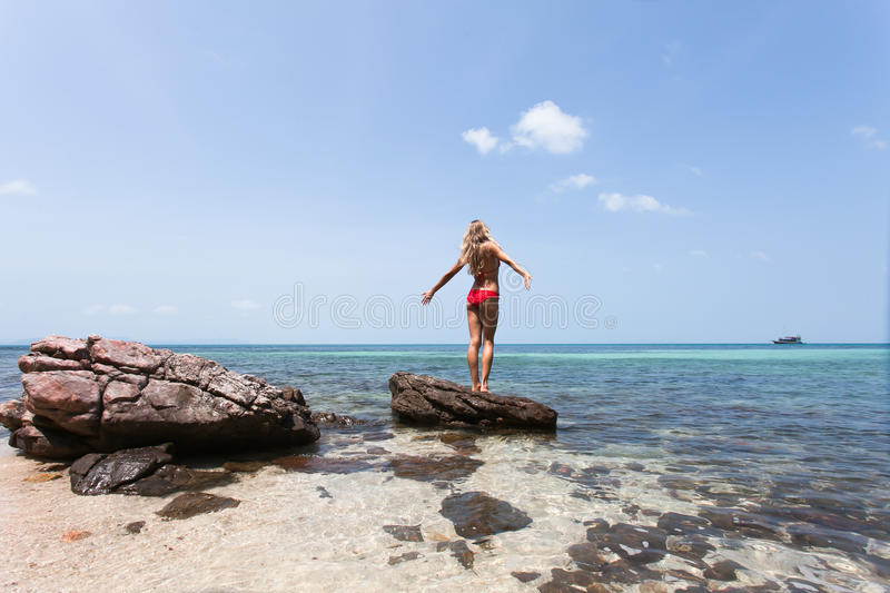 Beautiful Girl White Hair and red swimmingsuit staying on rock beach, relaxing and enjoy freedom. stock photo