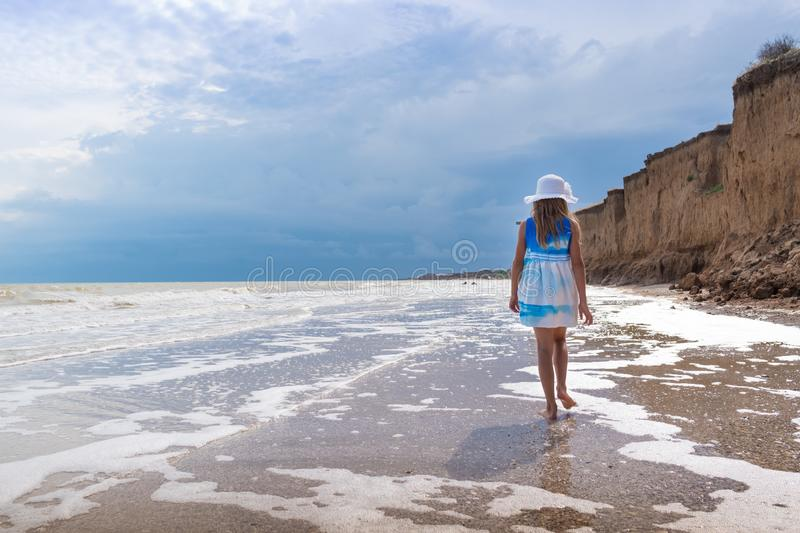 Beautiful girl in white hat and colorful dress on the seashore over blue sky background.  stock images