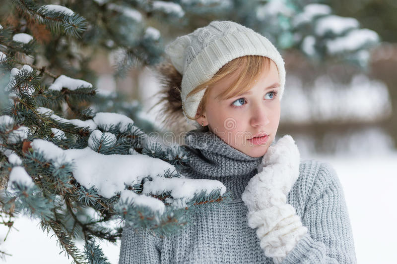 Download Beautiful Girl In A White Hat And Mittens In The Winter Snowy Fo Stock Photo - Image: 83719060