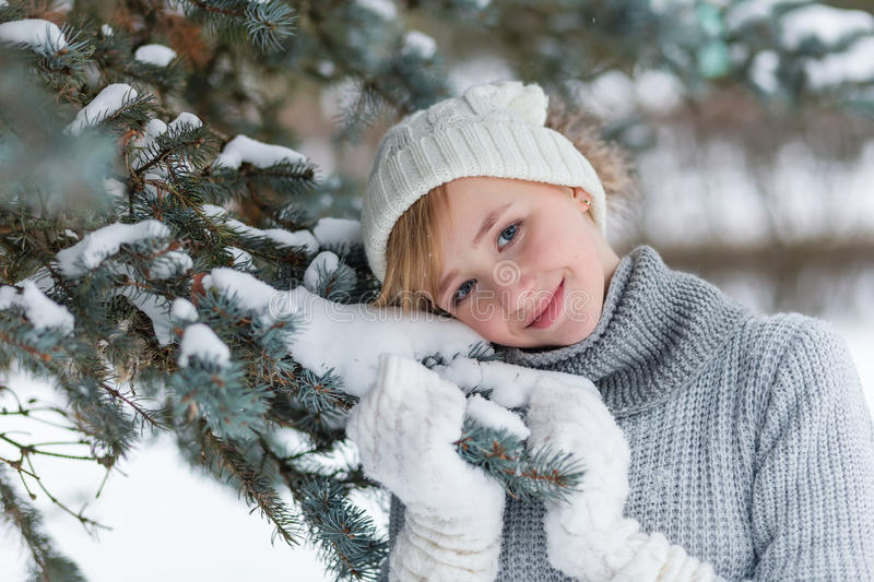 Download Beautiful Girl In A White Hat And Mittens In The Winter Snowy Fo Stock Photo - Image: 83719730