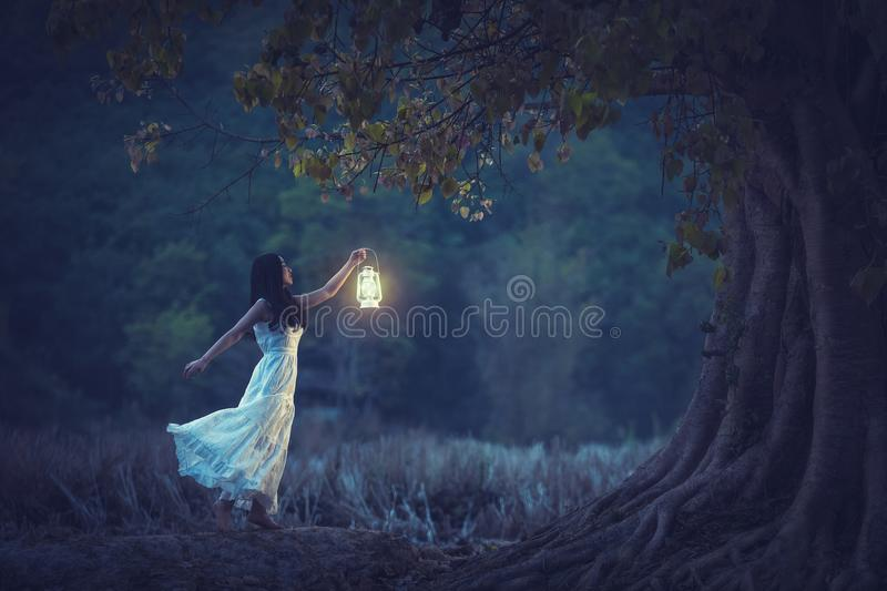 Beautiful girl in white holding a lantern in the autumn forest s royalty free stock photos