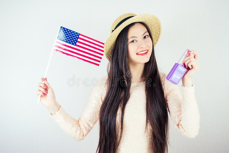 Beautiful girl in a white jacket holds an American flag and a small suitcase on a white background. The idea of stock photography
