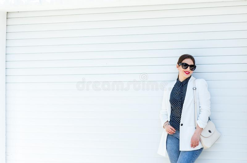 Beautiful Girl in White Jacket and Jeans at White Garage Wall Background. Trendy Casual Fashion Outfit in Summer. royalty free stock photography