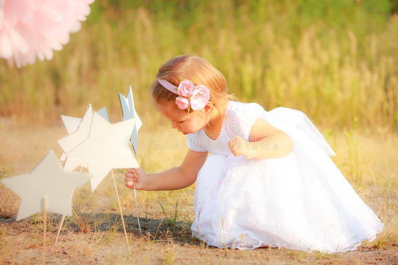 Beautiful girl in white long dress puts paper star on ground. Child on background of nature. stock photo