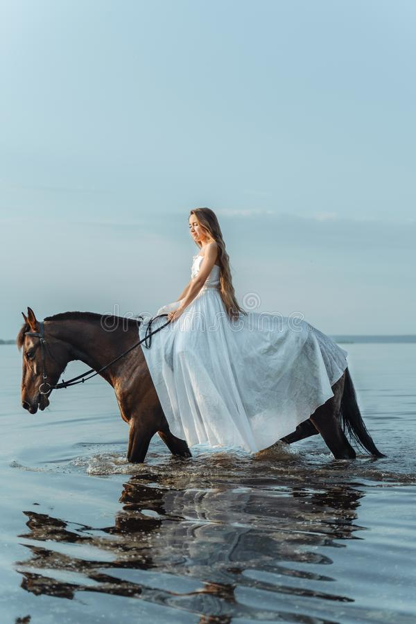 Beautiful girl in a white long dress riding a horse. Bride in the lake on horseback. Beautiful girl in a white long dress riding a horse. Bride in the lake on royalty free stock photo