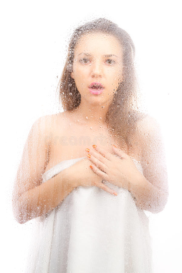 Beautiful Girl In A White Sheet Behind A Wet Glass Stock Photo