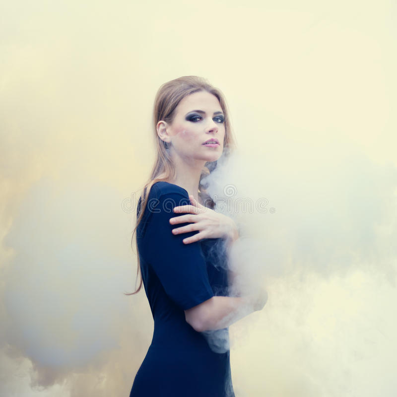 Beautiful girl in white smoke stock image