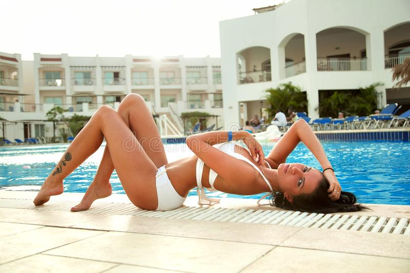 Beautiful girl in a white swimsuit sunbathing by the pool. royalty free stock photo
