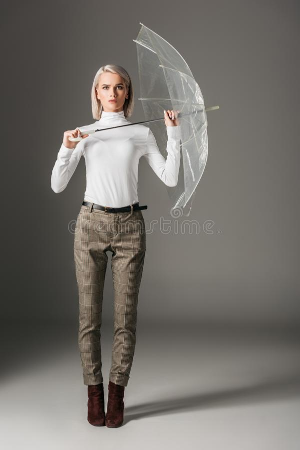 Beautiful girl in white turtleneck and grey pants holding transparent umbrella. On grey royalty free stock photography