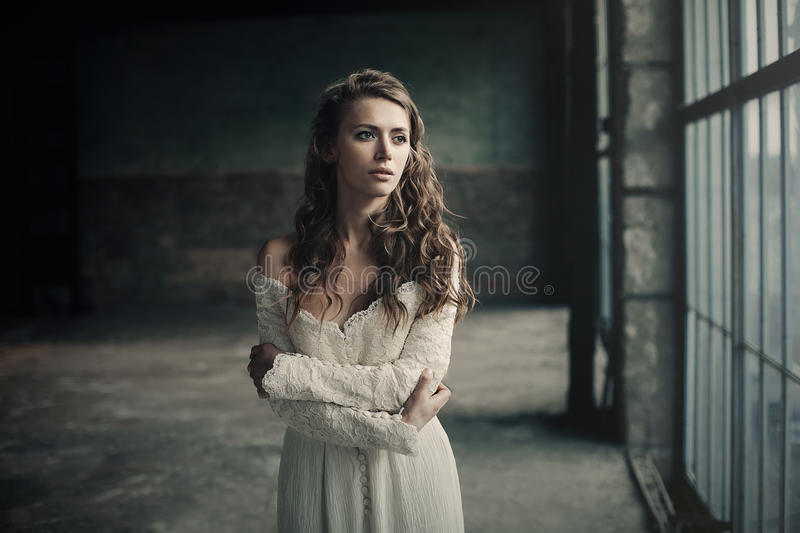 Beautiful girl in in white vintage dress with curly hair posing near the loft window. Woman in retro dress. Worried sensual emotio stock photo