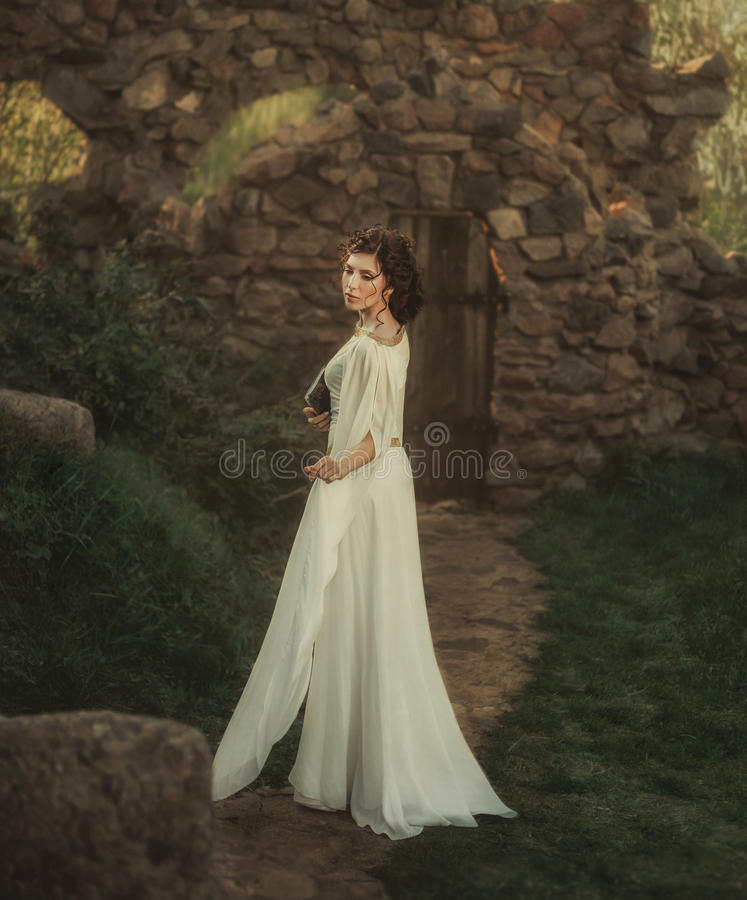 A beautiful girl in a white vintage dress stock photography