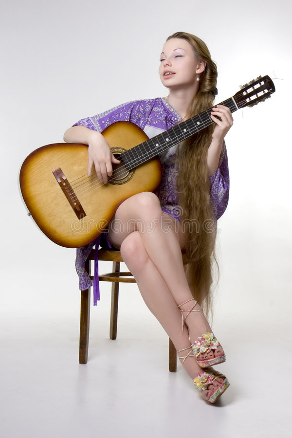 Beautiful girl who plays the guitar stock photo