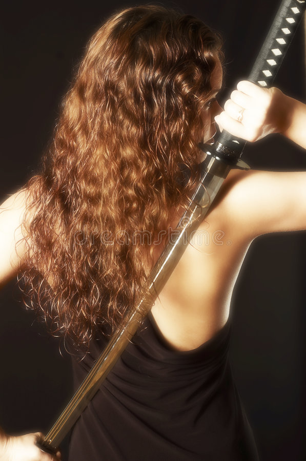 Beautiful girl will get because katana of back. The beautiful girl in black a dress with Japanese sword stock photos