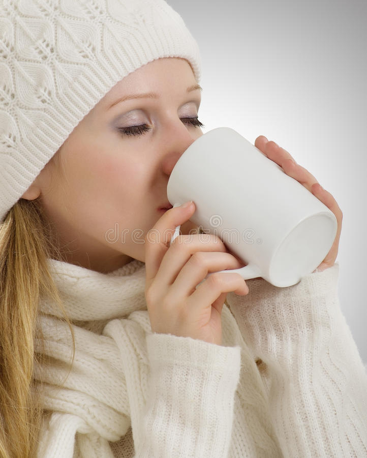 Beautiful girl in winter clothes drinking drink royalty free stock photo